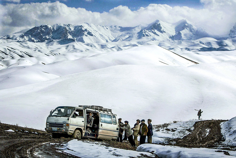 A hired van from Bamiyan, Afghanistan heading to the mountain town of Yawkalang is stuck in the mud along the high mountain single track primitave road recently demined by international mine clearing teams.  Some of the last fighting during the Afghan civil war took place when the Taliban capturing Bamiyan and Yawkalang late in September 1998 with heavy mine laying campaigns conducted in the region.  With winter conditions making the roads nearly impossible to drive except by four wheel drive vehicles, straying off the narrow road will put the travelers in jeopardy from mines which have not been cleared from the sides of the roads and other roads not yet demined.<br /> <br />Road repair projects sponsored by foreign aid groups providing money or food for work, pay for local men and boys equipped with pick axes and shovels attempting to manage snow and ice covered roads from 8000 feet up and over the Shatoo Pass at 13,500 feet. <br /><br />Workers from neighboring villages walk for hours to work along the road leading from the central highlands of the Afghanistan village of Yawkalang--nearly 80 km west of Bamiyan--to the top of the 13,500 foot Shatoo Pass and work in the snow attempting to keep the primitive dirt/mud road open though the winter for the first time in recorded history.  Afghan President Hamid Karzai has promised the country that road improvements are a main priority but with limited funding to repair and maintain roads--nearly all unpaved--that have been destroyed by years of war, progress could take years.