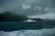 From the window of a passing ferry, a Philippine Coast Guard vessel is seen at sea during rainy season off the coast of El Nido, Palawan, Philippines.