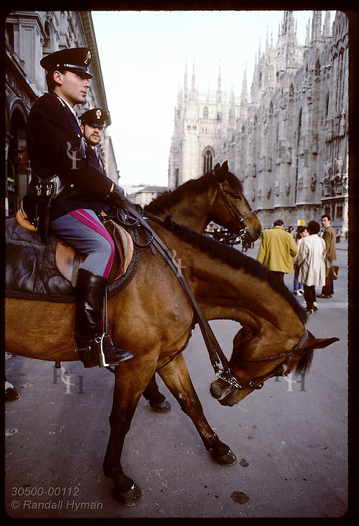 Horse pulls against reins and bows as two equestrian cops patrol street by Duomo Cathedral; Milan Italy