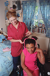 Care manager in residential care centre styling hair for young woman with Cerebral Palsy,
