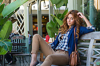 Portrait of young fashionable woman seating outside a store