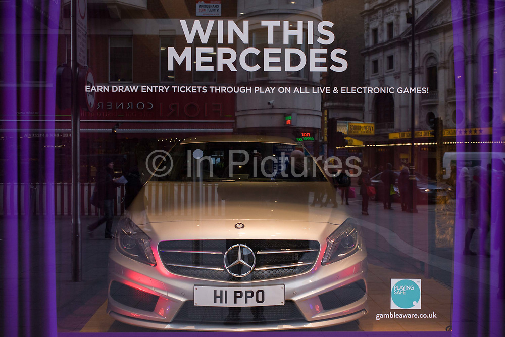 Win this Mercedes in a central London amusement arcade, a temptation for gamblers to enter an electronic draw. The bonnet (hood) of the supercar is pointed out towards passers-by in the street, a clear ploy to attract them inside to spend their money on a risk worth taking. The URL for the gambling support group 'gambleaware.co.uk' is carefully positioned in the corner to allow potential risk takers to decide on how to gamble responsibly. Some people gambling can become a serious problem, both for themselves and for their family, friends, and those concerned about them. Gambleaware provide tools to help them to recognise problem gambling behaviour.