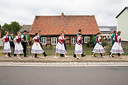 Heimat & Brauchtum Series: Johannisreiten in Casel, Brandenburg, with Marcel as the Johannis and a dance the night before.<br /> <br /> Sorbian girls in traditional costume are sewing the 'Johann' into a floral dress of blue cornflowers. Sorbian women are weaving rushes into a crown adorned with bouquets of different flowers.<br /> The rushes along with water lilies have been picked by a group of young men in the early morning hours. At around 5am they went deep into the woods, wading through ponds to pick the best plants.<br /> <br /> The crown always has cornflowers, rushes, roses and water lilies because of its specific healing effects. Legend has it, if they are picked on this specific day of the Nativity of Saint John the Baptist on June 24th (Johannistag related to Johannis der Täufer), the effects of the flowers are even stronger.<br /> <br /> The Johannis has to ride on his horse, people of the village have to pull him off of his horse, stealing his crown and picking his cornflowers from his suit.<br /> <br /> This Sorbian tradition has its origins many hundreds of years ago. It was first mentioned on a written record from 1880 with pointing out, that this tradition has been celebrated since many generations when people still worshiped Germanian Gods and the Wenden and Sorbian people settled in this area. <br /> With the Christianization, this pagan tradition has been linked to John the Baptist.  <br /> <br /> Since after the war 1945/46 the Johannisreiten has been celebrated every year, even through the suppression of the Sorbian Minority in times of the DDR.<br /> The tradition survived only in Case, because after the war, there were not enough men left in other villages.