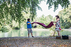 Couple spread out blanket for picnic at lakeshore in the English Garden, Munich, Germany