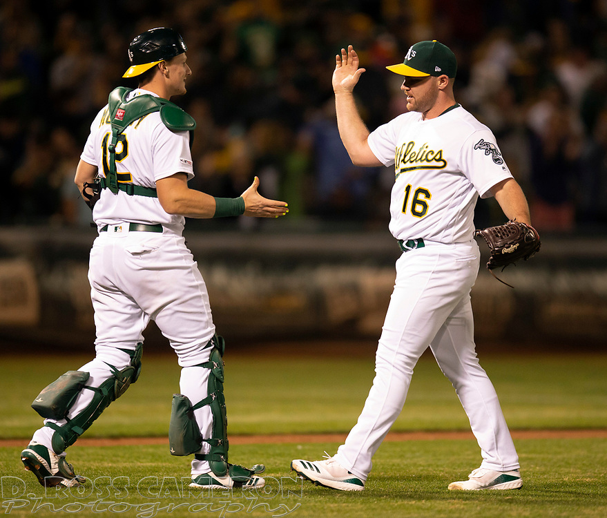 Sep 17, 2019; Oakland, CA, USA; Oakland Athletics catcher Sean Murphy (12) and pitcher Liam Hendriks celebrate their 2-1 victory over the Kansas City Royals in a baseball game at Oakland Coliseum. Mandatory Credit: D. Ross Cameron-USA TODAY Sports