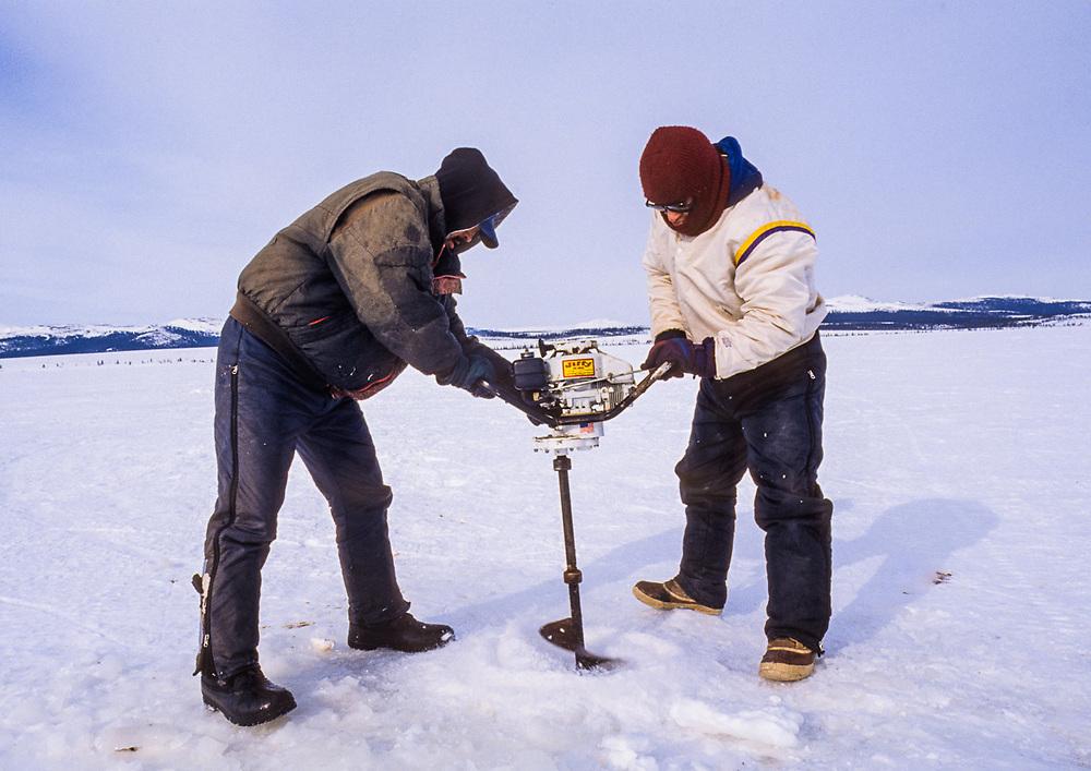 Eli and Daniel Williams drilling an ice fishing hole on Kobuk Lake, April, Kotzebue, Alaska, USA