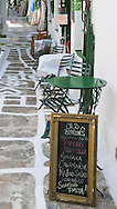 Menu sign and tables at ally cafe on the greek island of Ios, Greece.