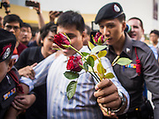 """14 FEBRUARY 2015 - BANGKOK, THAILAND: Student activist Siriwit Serithiwat holds up a rose while he is led away by police after he was arrested during a protest the military coup. Martial law is still in effect in Thailand and protests against the coup are illegal. Dozens of people gathered in front of the Bangkok Art and Culture Centre in Bangkok Saturday to hand out red roses and copies of George Orwell's """"1984."""" Protestors said they didn't support either Red Shirts or Yellow Shirts but wanted a return of democracy in Thailand. The protest was the largest protest since June 2014, against the military government of General Prayuth Chan-Ocha, who staged the coup against the elected government. Police made several arrests Saturday afternoon but the protest was not violent.      PHOTO BY JACK KURTZ"""