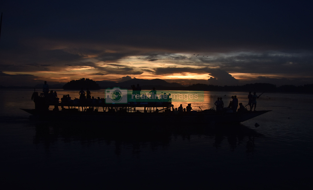 June 28, 2017 - Guwahati, India - Indian vendors walk at the bank of the river Brahmaputra, as they came to catch a boat to return home, as monsoon clouds hover in the sky in Guwahati city. According to reports, torrential monsoon showers caused flash flooding in parts of Assam. (Credit Image: © Rajib Jyoti Sarma/Pacific Press via ZUMA Wire)