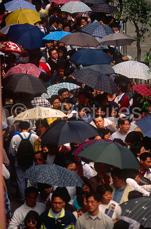 Hong Kong-born Chinese queue outside ImmigrationTower to apply for naturalisation as British Dependent Territories Citizens, one year before the handover of sovereignty from Britain to China, on 29th March 1996, in Hong Kong, then a British colony but latterly, China.