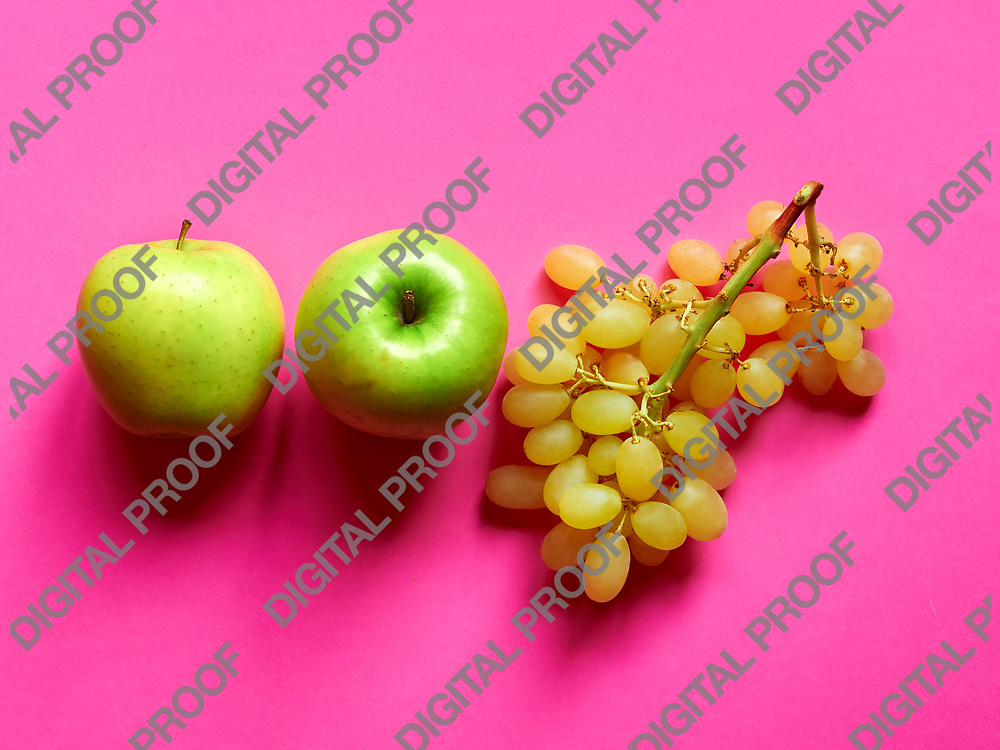 Above view of isolated set of a green apple with a bunch of sweet seedless grapes in studio with pink background