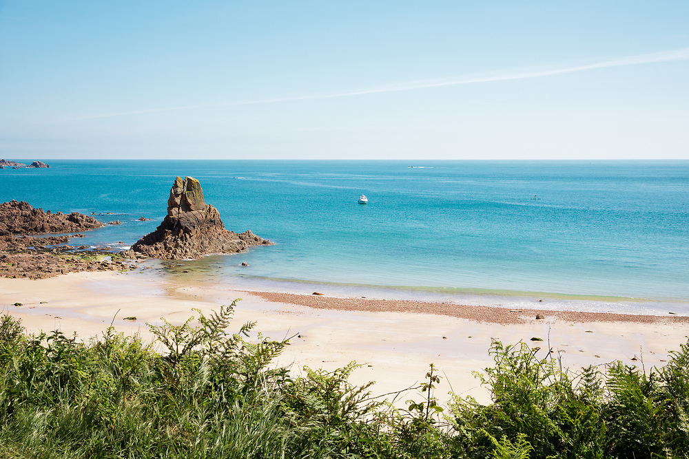 Calm, blue water at Beauport beach in summer, a hidden cove on the south coast of Jersey, Channel Islands