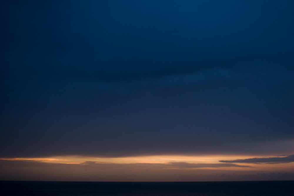 The last sliver of light escapes through clouds as night falls.