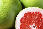 Close up selective focus photograph of a group of Red Pomelos with one cut open