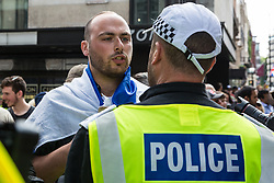 London, UK. 10th June, 2018. A man draped in an Israeli flag has a discussion with a police officer before the pro-Palestinian Al Quds Day march through central London organised by the Islamic Human Rights Commission. An international event, it began in Iran in 1979. Quds is the Arabic name for Jerusalem.