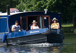 © Licensed to London News Pictures. 15/06/2021. Henley-on-Thames, UK. Three women relax on a barge as it makes its way along the River Thames at Henley-on-Thames in Oxfordshire on a hot summer's morning. Photo credit: Ben Cawthra/LNP