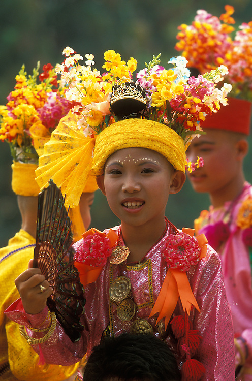 Attendants carry boys dressed up as princes on their shoulders at Poy Sang Long, the yearly ordination of novice monks in Mae Hong Son, Thailand.