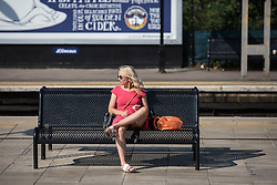 © Licensed to London News Pictures. 01/07/2015. London, UK. A woman waits in the sun at Watford Junction this morning which saw commuters and tourists struggle with the intense heat on the rail network this morning (01/07) on what is set to be the hottest day this decade. Photo credit : James Gourley/LNP