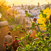 Two people walking down the hills of the Alhambra at the end of the day.