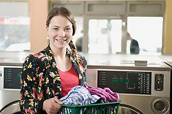 Portrait of young woman holding laundry basket, smiling