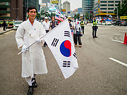 09 JUNE 2018 - SEOUL, SOUTH KOREA: A man in traditional clothes with a South Korean flag marches in a pro-American rally in downtown Seoul. Participants said they wanted to thank the US for supporting South Korea and they hope the US will continue to support South Korea. Many were also opposed to ongoing negotiations with North Korea because they don't think Kim Jong-un can be trusted to denuclearize or to not attack South Korea.     PHOTO BY JACK KURTZ
