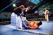 Female wrestler and referee pulling off opponents trousers whilst on the floor of ring. Lucha Libre wrestling origniated in Mexico, but is popular in other latin Amercian countries, including in La Paz / El Alto, Bolivia. Male and female fighters participate in the theatrical staged fights to an adoring crowd of locals and foreigners alike.