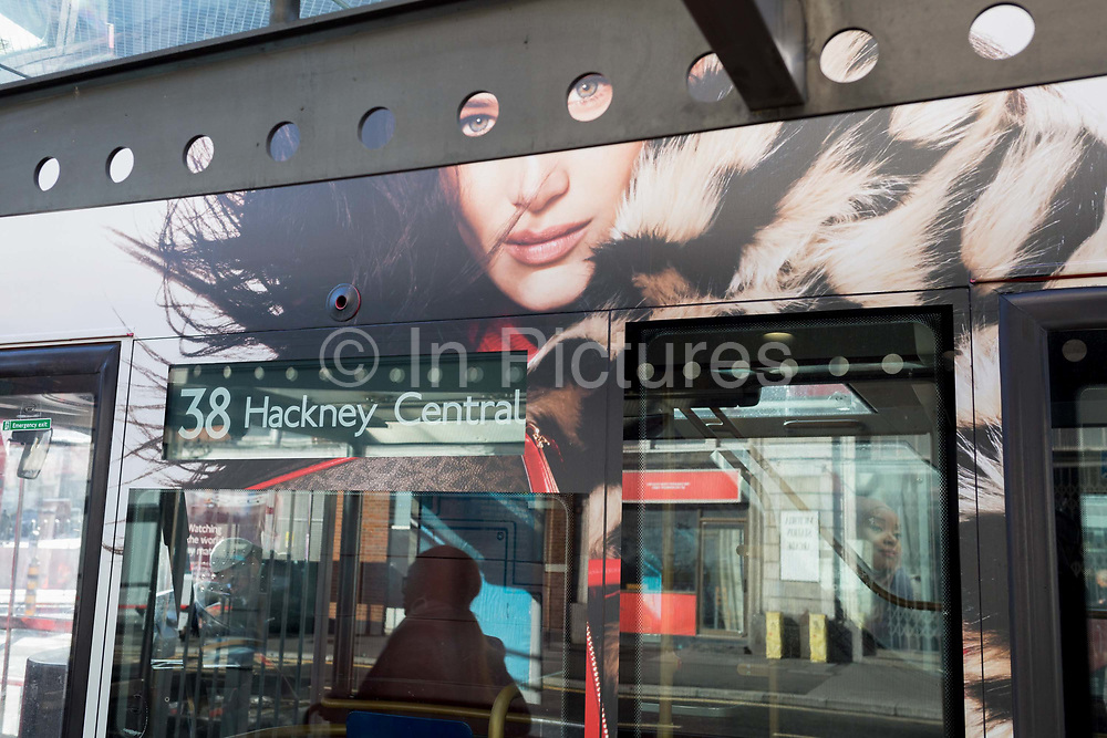 The eyes of a model on the side of a London bus, that features an ad of style and fashion, peer through round apertures of a bus station shelter roof, while stopped at Victoria Station, on 18th October 2019, in London, England.