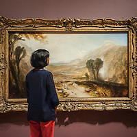 London, UK - 8 September 2014: a gallery assistant looks up at 'Story of Apollo and Daphne' <br />  by J.M.W. Turner, during the press preview of The EY Exhibition: Late Turner – Painting Set Free exhibition at Tate Britain