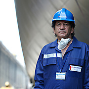 portriat of a man working in a shipyard in Dubai with ships and workers in the background