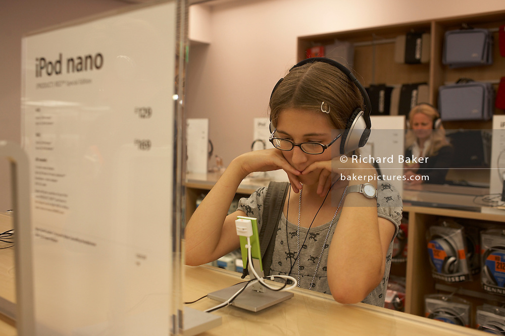 A twelve year-old girl visiting the London branch of the Apple Store in London's Regent Street, is listening intently to digital music on a green iPod Nano. She is concentrating on the music playing through her headphones and resting her elbows on the desk top furniture. In front of her is a price list for this audio gadget. telling us that is costs £129.  The girl's hair is parted in the middle of her head and she wears a clip to keep her hair from her face. Over her shoulders is a display of headsets on a rack and in the background an older lady is also listening to music through another device.