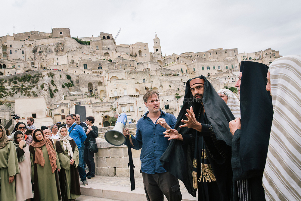 """MATERA, ITALY - 5 OCTOBER 2019: Director Milo Rau (42, center) is seen here in the backstage of the scene of the encounter of Jesus Christ with the Pharisees in his film  """"The New Gospel"""",in Matera, Italy, on October 5th 2019.<br /> <br /> Theatre Director Milo Rau filmed the Passion of the Christ  under the title """"The New Gospel"""" with a cast of refugees, activists and former actors from Pasolini and Mel Gibson's films.<br /> <br /> The role of Jesus is performed by Yvan Sagnet, a Political activist born in Cameroon and who worked on a tomato farm when in 2011 he revolted against the system of exploitation and led the first farm workers' strike in southern Italy. In a series of public shoots in the European Capital of Culture Matera, Jesus will proclaimed the Word of God, was crucified (October 6th 2019) and finally rose from the dead in Rome, the capital of Catholic Christianity and seat of one of the most xenophobic governments in Europe (October 10th 2019).<br />  <br /> Parallel to the film, the humanistic message of the New Testament was transformed into the present: at the beginning of September, the campaign """"Rivolta della Dignità"""" (Revolt of Dignity), which demanded fair working and living conditions     for refugees, global freedom of travel and civil rights for all, started with a march from the southern Italian refugee camps. """"It's about putting Jesus on his feet,"""" director Milo Rau said. Led by Jesus actor Yvan Sagnet, the campaign fights for the rights of migrants who came to Europe via the Mediterranean to be enslaved by the Mafia in the tomato fields of southern Italy and to live in ghettos under inhumane conditions. The campaign and the film thus create a """"New Gospel"""" for the 21st century, a manifesto of solidarity with the poorest, a revolt for a more just and humane world."""