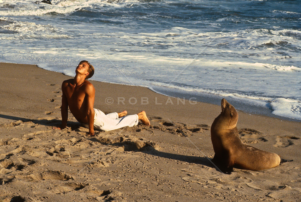 shirtless man imitating a sea lion on the shore of the Pacific Ocean, California