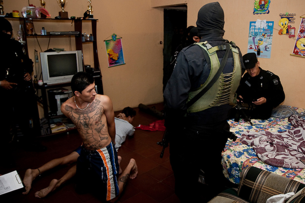 Police question two members of MS-13, the largest gang in El Salvador during an early morning raid in the impoverished Parieso Barrio in San Salvador.  Under the recent Mano Duro and Super Mano Duro policies (hard hand) police have been given broad authority to enter private houses and make arrests to suppress the rapidly growing MS-13 and 18th street gangs.