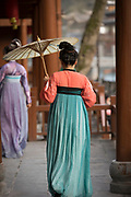 Rear view of a walking woman in a traditional Chinese dress and with an umbrella, Fenghuang, Hunan Province, China