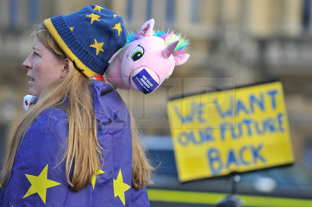 """© Licensed to London News Pictures. 30/01/2018. LONDON, UK.  A campaigner stands outside the Houses of Parliament to protest against Brexit carrying a toy unicorn bearing with the message """"We Were Conned"""".  It has been reported that a leaked document entitled """"EU Exit Analysis - Cross Whitehall Briefing"""", drawn up by the Department for Exiting the EU, concludes that Britain will be worse off under any Brexit scenario.   Photo credit: Stephen Chung/LNP"""