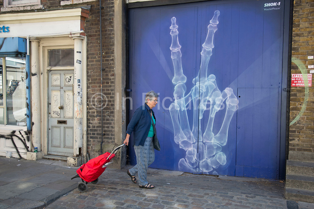 Street art x-ray hand giving the 'V' sign by Shok-1 in the Brick Lane area of Shoreditch, East London, United Kingdom. Street art in the East End of London is an ever changing visual enigma, as the artworks constantly change, as councils clean some walls or new works go up in place of others. While some consider this vandalism or graffiti, these artworks are very popular among local people and visitors alike, as a sense of poignancy remains in the work, many of which have subtle messages. (photo by Mike Kemp/In Pictures via Getty Images)
