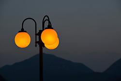 THEMENBILD - Die Lombardei ist eine norditalienische Region mit einer Fläche von 23.863 km und ca.9,8 Mio. Einwohnern. Sie ist in zwölf Provinzen aufgeteilt und liegt zwischen Lago Maggiore, Po und Gardasee. Bilder aufgenommen am 21. August 2013, im Bild Abendstimmung, beleuchtete Strassenlaternen, Blick von der italienischen Seite des Luganersee, Lago di Lugano, auf das UNESCO Weltkulturerbe Monte San Giorgio im Tessin, Schweiz, Porto Ceresio // THEMES PICTURE - Lombardy is a northern Italian region with an area of 23,863 km and a population of 9,8 Mio. It is divided twelve provinces and is situated between Lake Maggiore, Lake Garda and Po. Pictured on 2013/08/21. EXPA Pictures © 2013, PhotoCredit: EXPA/ Eibner/ Michael Weber<br /> <br /> ***** ATTENTION - OUT OF GER *****