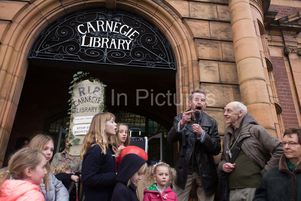 English novelist Adam Mars-Jones speaks passionately to a crowd outside Carnegie Library in Herne Hill. Faced with the closure of its beloved local library, the people of Lambeth, south London hold a demonstration outside the Edwardian-era building. Lambeth council plan to close the facility used by the community as part of austerity cuts, saying they will convert the building into a gym and privately-owned gentrified businesses - rather than a much-loved reading and learning resource. £12,600 was donated by the American philanthropist Andrew Carnegie to help build the library which opened in 1906. It is a fine example of Edwardian civic architecture, built with red Flettan bricks and terracotta, listed as Grade II in 1981. 3