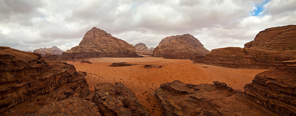 Sandstone cliffs rise from the red sand in Burrah Canyon, Wadi Rum, Jordan.