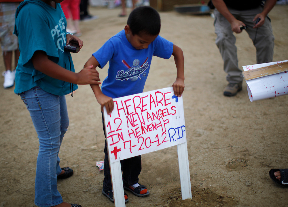 A young boy places a new sign at a memorial to those killed in Aurora, Colorado July 28, 2012. Four more funerals for victims were held today across the country.  REUTERS/Rick Wilking (UNITED STATES)