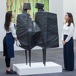 "© Licensed to London News Pictures. 16/11/2018. LONDON, UK. Staff members view ""Two Watchers V Third Version"" by Lynne Chadwick (Est. GBP400,000-600,000).  Preview of Sotheby's autumn sale of Modern & Post War British art.  Works from the British art scene of the past century will be offered for sale on 20 and 21 November 2018 at Sotheby's in London.  Photo credit: Stephen Chung/LNP"