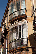 A large window, architectural detail, of the corner of an apartment block in downtown Malaga, Spain