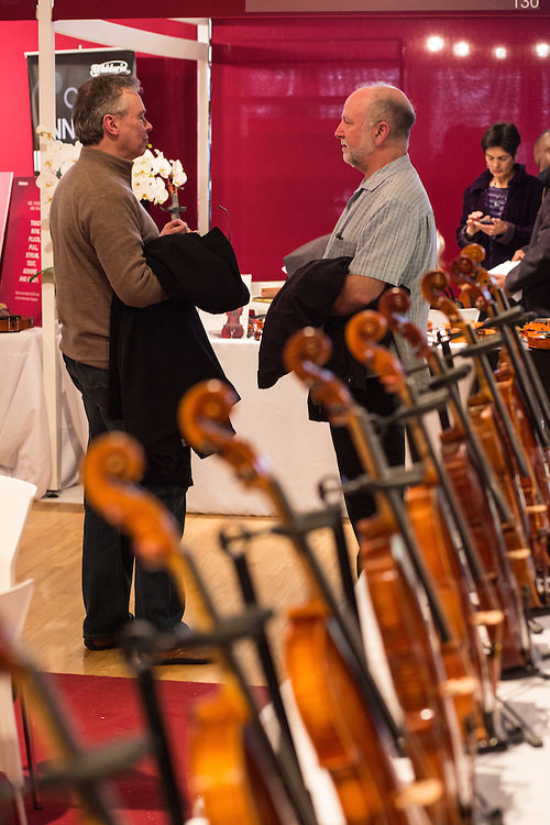 Visitors framed by violins discuss the show.