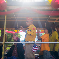 081415       Cable Hoover<br /> <br /> Navajo Codetalker John Kinsel waves to the crowd as he rides in a float during the Codetalker Day parade Friday in Window Rock.