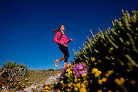 Woman running in mountains with ocean in the background. Female runner, jogging and exercising outdoors in nature, rocky trail with plants.