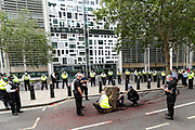 Protest Removal police team talk to two members of extinction Rebellion activists who glued themselves outside Home Office in central London on Wednesday, Sept 2, 2020. Environmental activist group XR enters its 2nd day of climate change demonstrations, which they began on the first week of September. (VX Photo/ Vudi Xhymshiti)