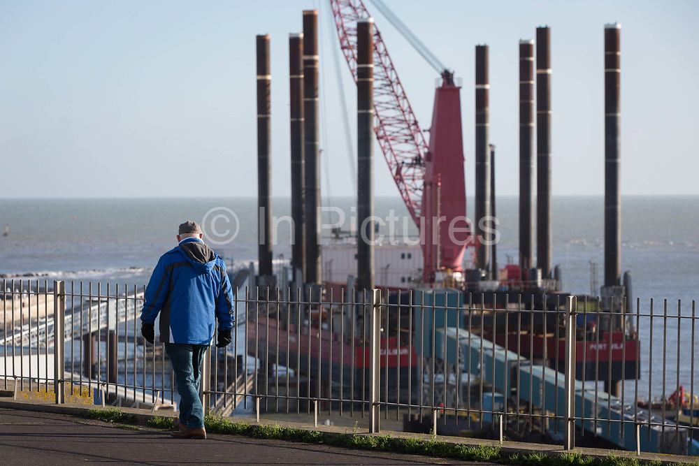 A Kent man walks along West Cliff Promenade that overlooks the Port of Ramsgate, a closed but once busy ferry terminal, on 8th January 2019, in Ramsgate, Kent, England. The Port of Ramsgate has been identified as a Brexit Port by the government of Prime Minister Theresa May, currently negotiating the UKs exit from the EU. Britains Department of Transport has awarded to an unproven shipping company, Seaborne Freight, to provide run roll-on roll-off ferry services to the road haulage industry between Ostend and the Kent port - in the event of more likely No Deal Brexit. In the EU referendum of 2016, people in Kent voted strongly in favour of leaving the European Union with 59% voting to leave and 41% to remain.