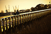 Couple walks along the marsh walk in Shem Creek, Mt Pleasant, SC across the harbor from Charleston.