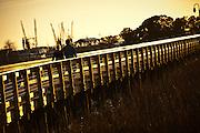 Couple walks along the marsh walk in Shem Creek, Mt Pleasant, SC across the harbor from Charleston.
