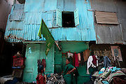 A woman stands in front of her home deep in the slum.  The slum of Cheetah Camp on the outskirts of Mumbai, India is a predominantly muslim community on living on the fringe while the city continues to grow.